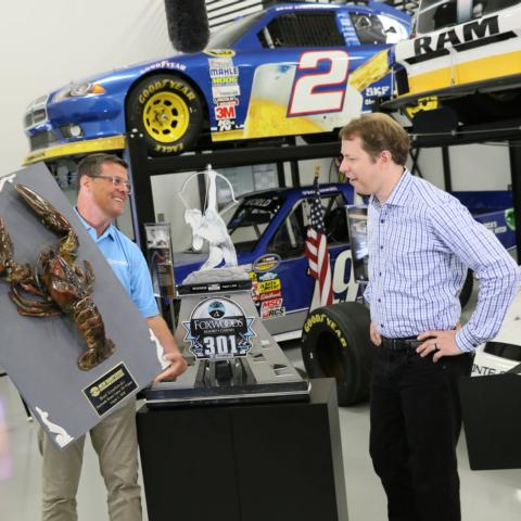New Hampshire Motor Speedway Executive Vice President and General Manager David McGrath (left) presents the 2020 Loudon the Lobster plaque to NASCAR Cup Series driver Brad Keselowski (right) on Wednesday. Keselowski earned the giant crustacean on Aug. 2, 2020 when he landed in victory lane for the Foxwoods Resort Casino 301.