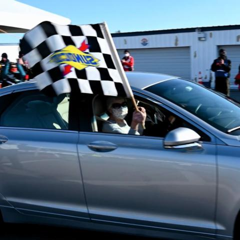 A Granite State couple waves the checkered flag after receiving the last COVID-19 vaccine shots at New Hampshire Motor Speedway's vaccine super site on March 8.