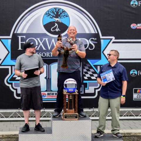 Billy Thomas (center) from WPKZ 105.3 FM/1280 AM in Fitchburg, Mass. won the fourth annual Media Racing Challenge at New Hampshire Motor Speedway Friday and was presented with a trophy, eight-pound live lobster and a $100 gift card to Makris Lobster and Steak House in Concord, N.H. Timmy G. (left) from The Wicked Fast Podcast on 105.7 WROR in Boston, Mass. came in second and Adam Drapcho (right) from the Laconia Daily Sun in Laconia, N.H. came in third.