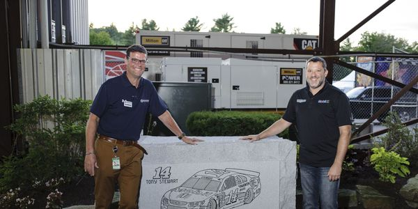 Tony Stewart and David McGrath hang out by the granite retirement gift NHMS gave Stewart.